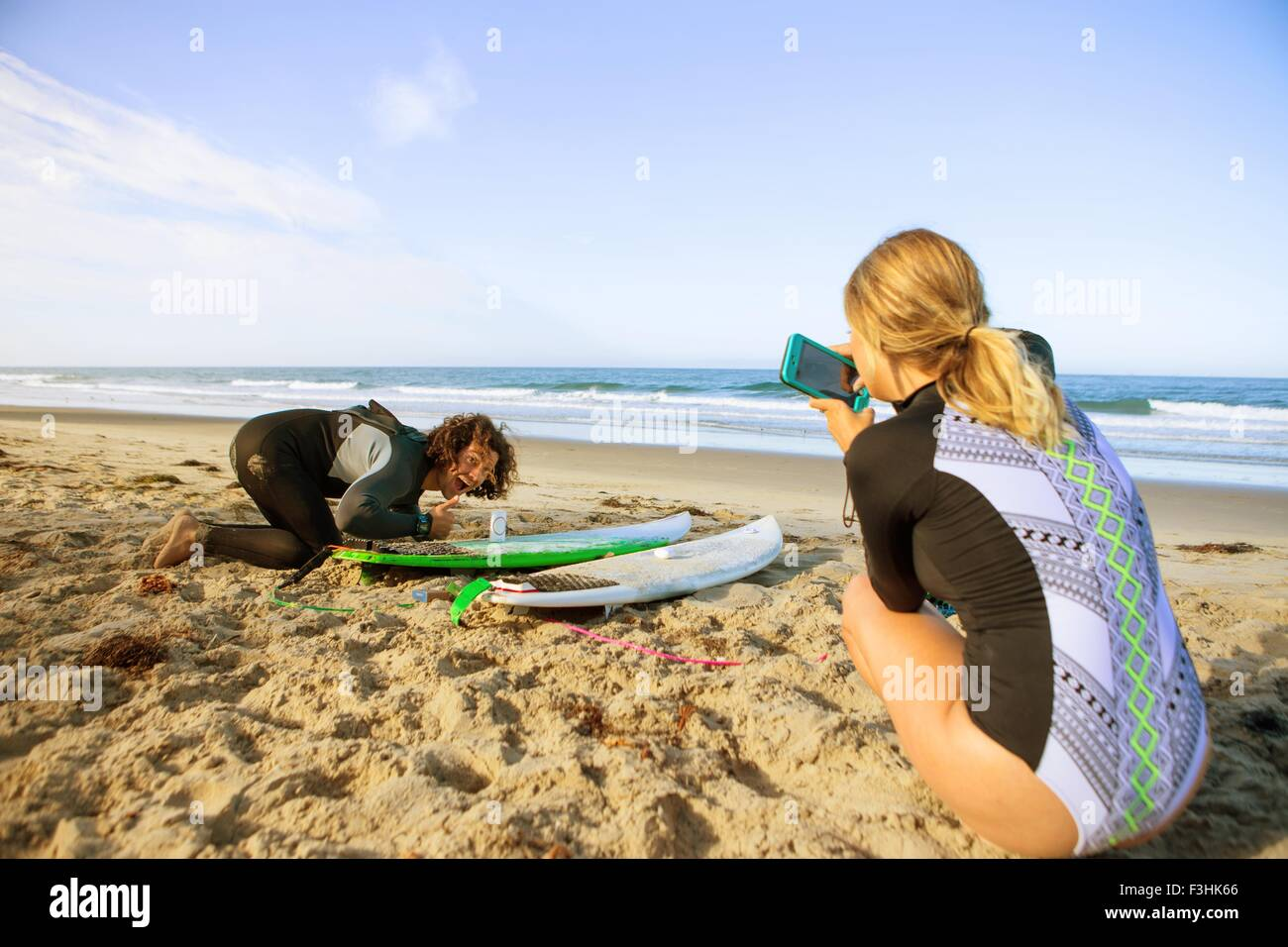 Couple on beach, young woman taking photograph of man with surfboard - Stock Image