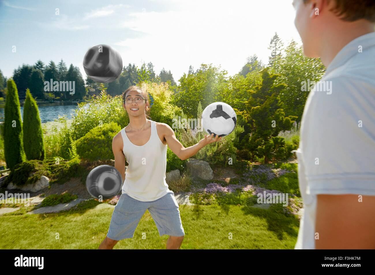Man juggling balls in field - Stock Image