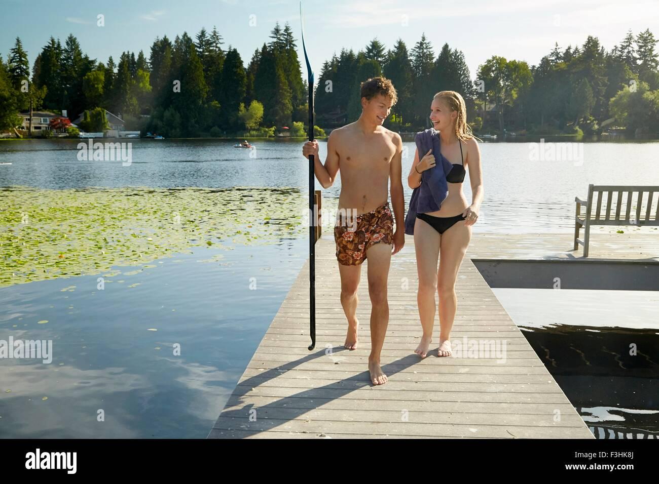 Couple leaving lake after swim, Seattle, Washington, USA - Stock Image