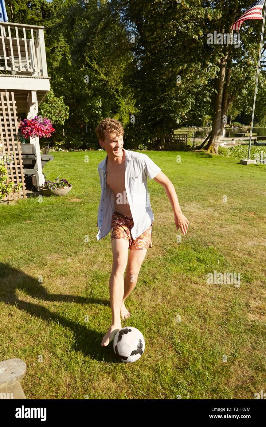 Man playing football in garden Stock Photo