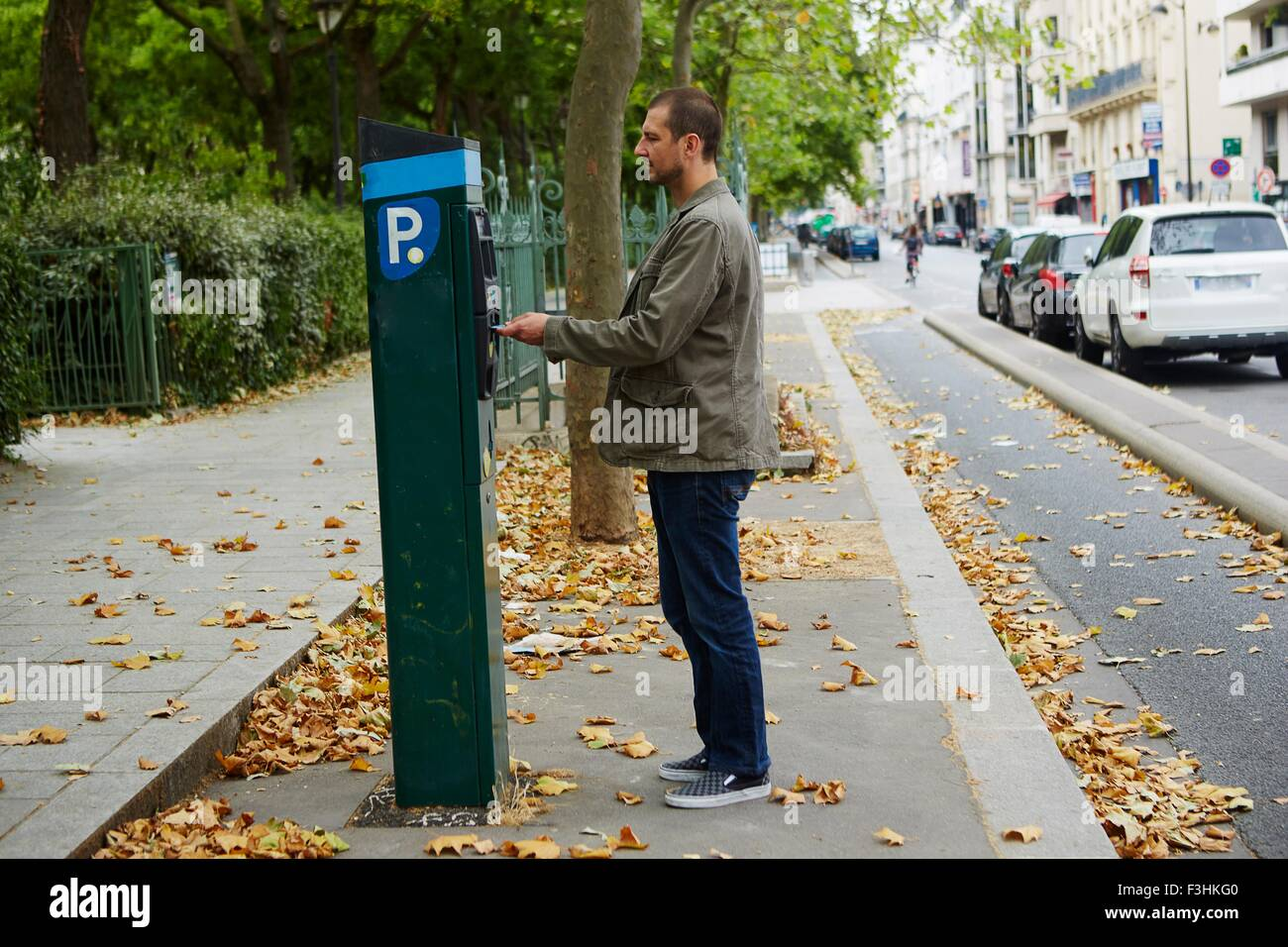 Mid adult man using parking meter in street - Stock Image