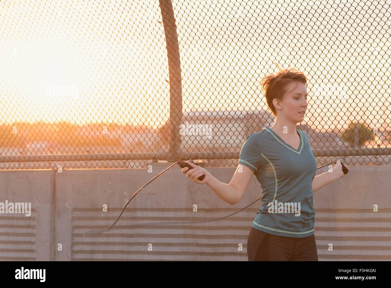 Mid adult woman, working out, skipping, outdoors - Stock Image