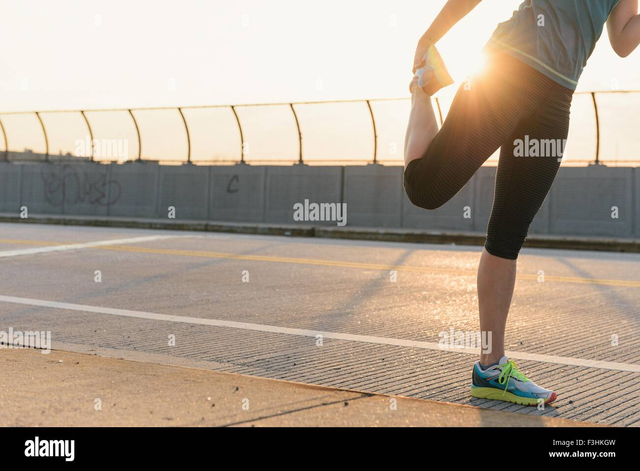 Mid adult woman, working out, stretching, outdoors, low section - Stock Image