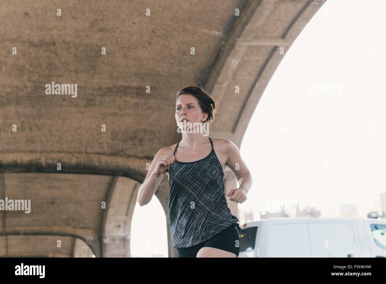 Mid adult woman, working out, running,, outdoors - Stock Image