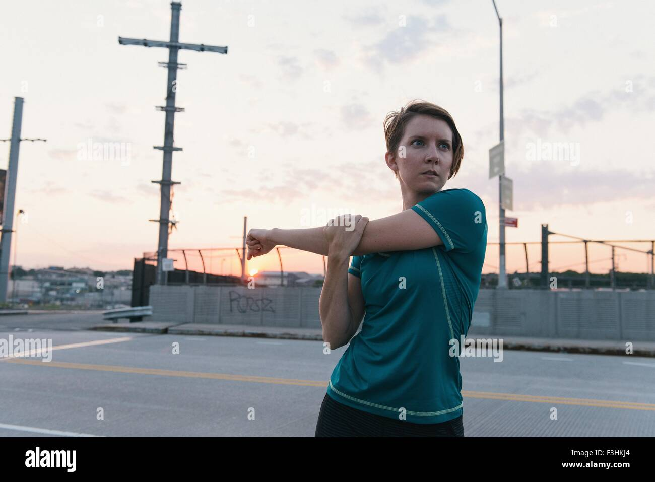 Mid adult woman, working out, stretching, outdoors - Stock Image