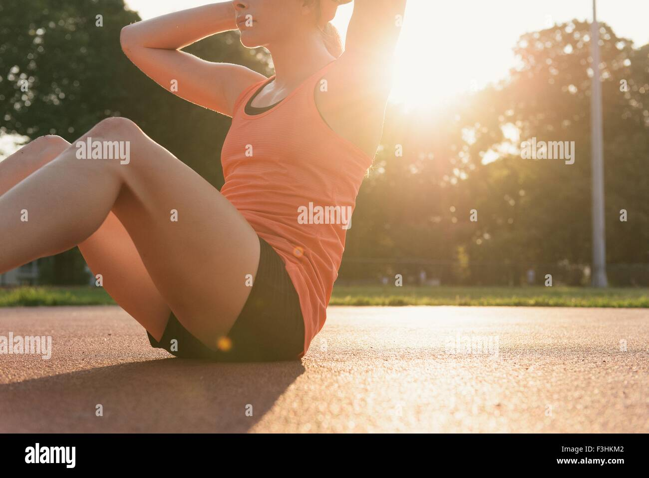 Young woman working out, doing sit-ups, outdoors - Stock Image