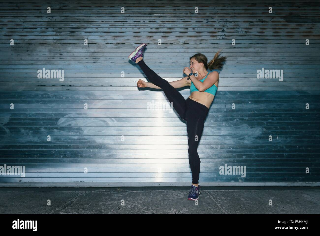 Young woman, working out, doing high kick, outdoors, at night - Stock Image