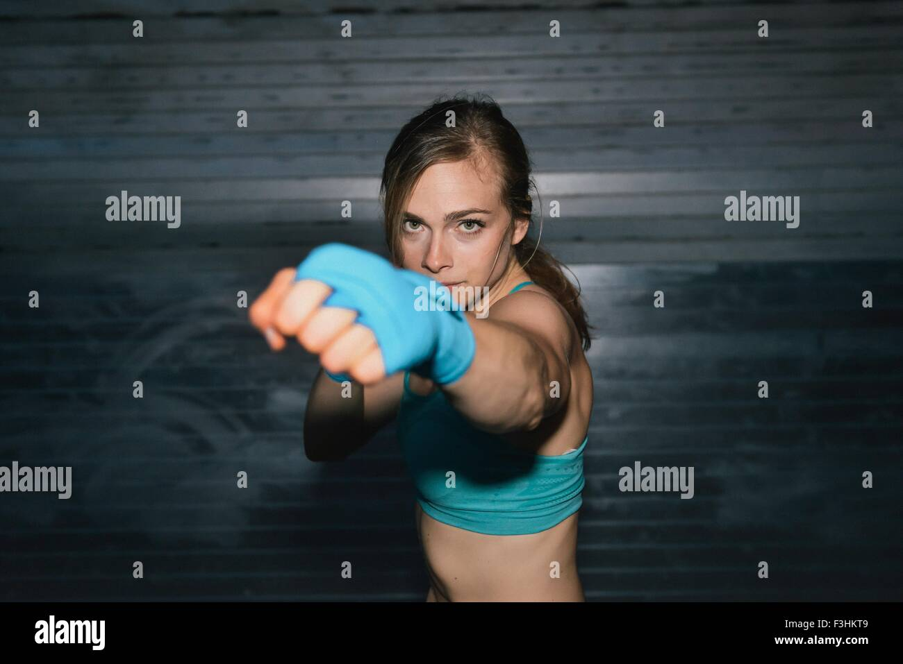 Young woman, working out, boxing, outdoors, at night - Stock Image