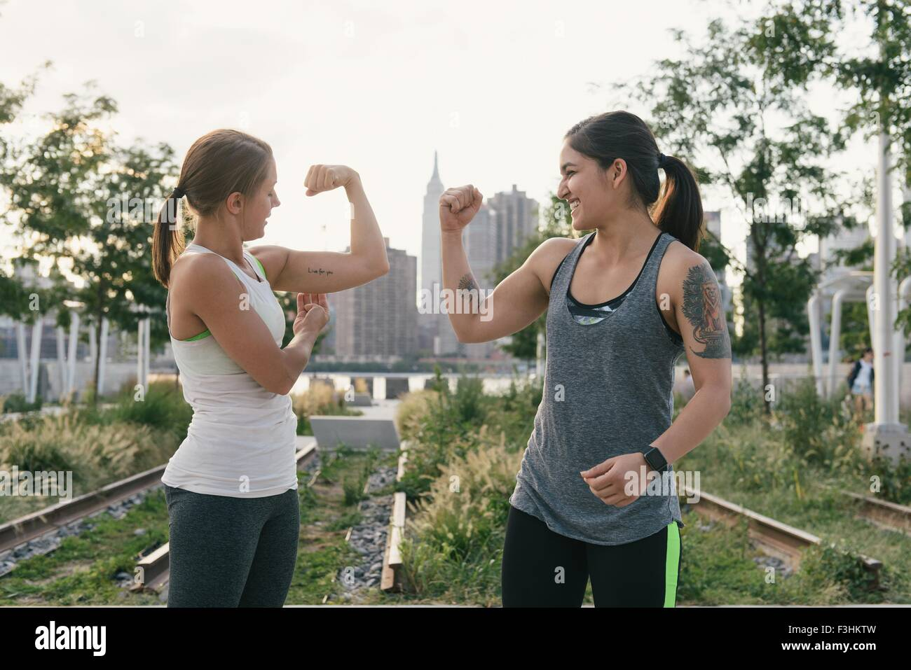 Two friends comparing bicep muscles - Stock Image