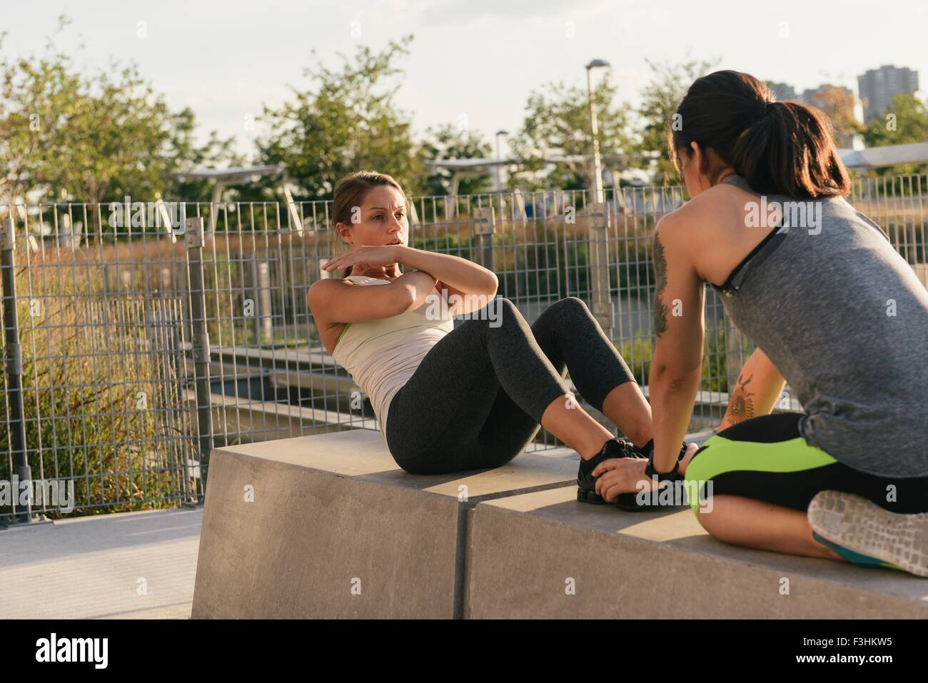 Two friends exercising together and helping to do sit ups - Stock Image