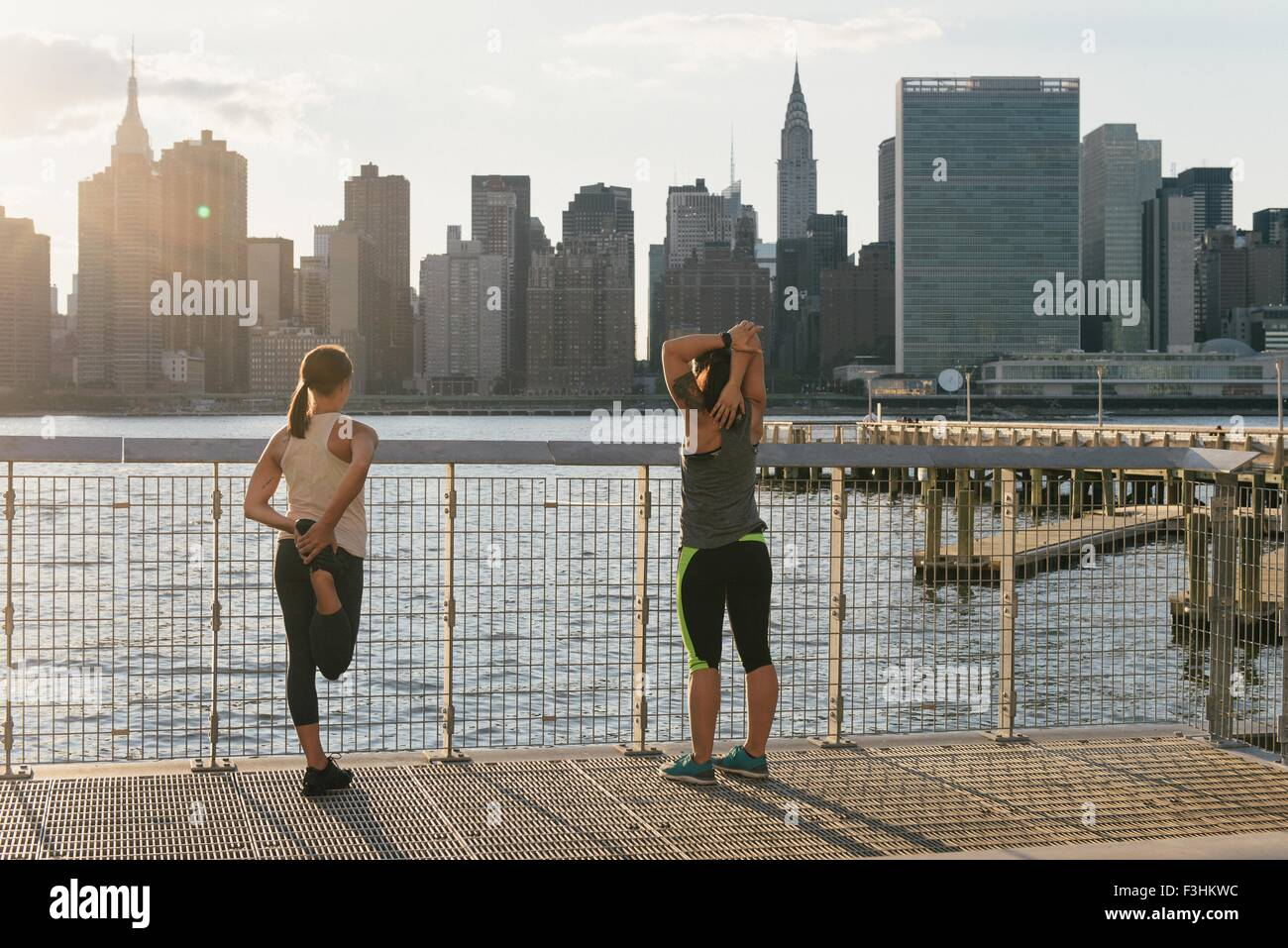 Two friends warming up to exercise together outdoors - Stock Image