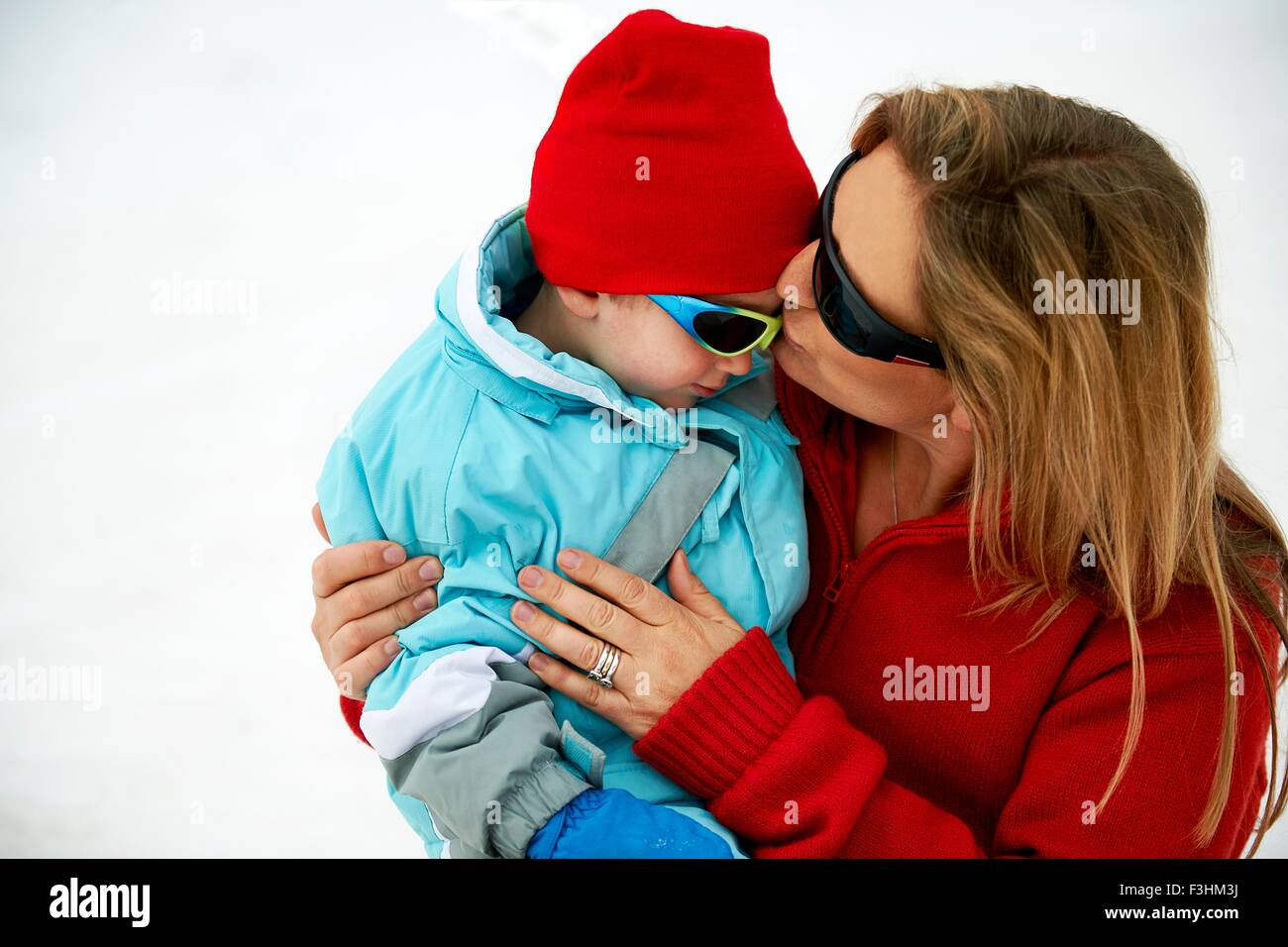 Skiing mother kissing toddler son on forehead - Stock Image
