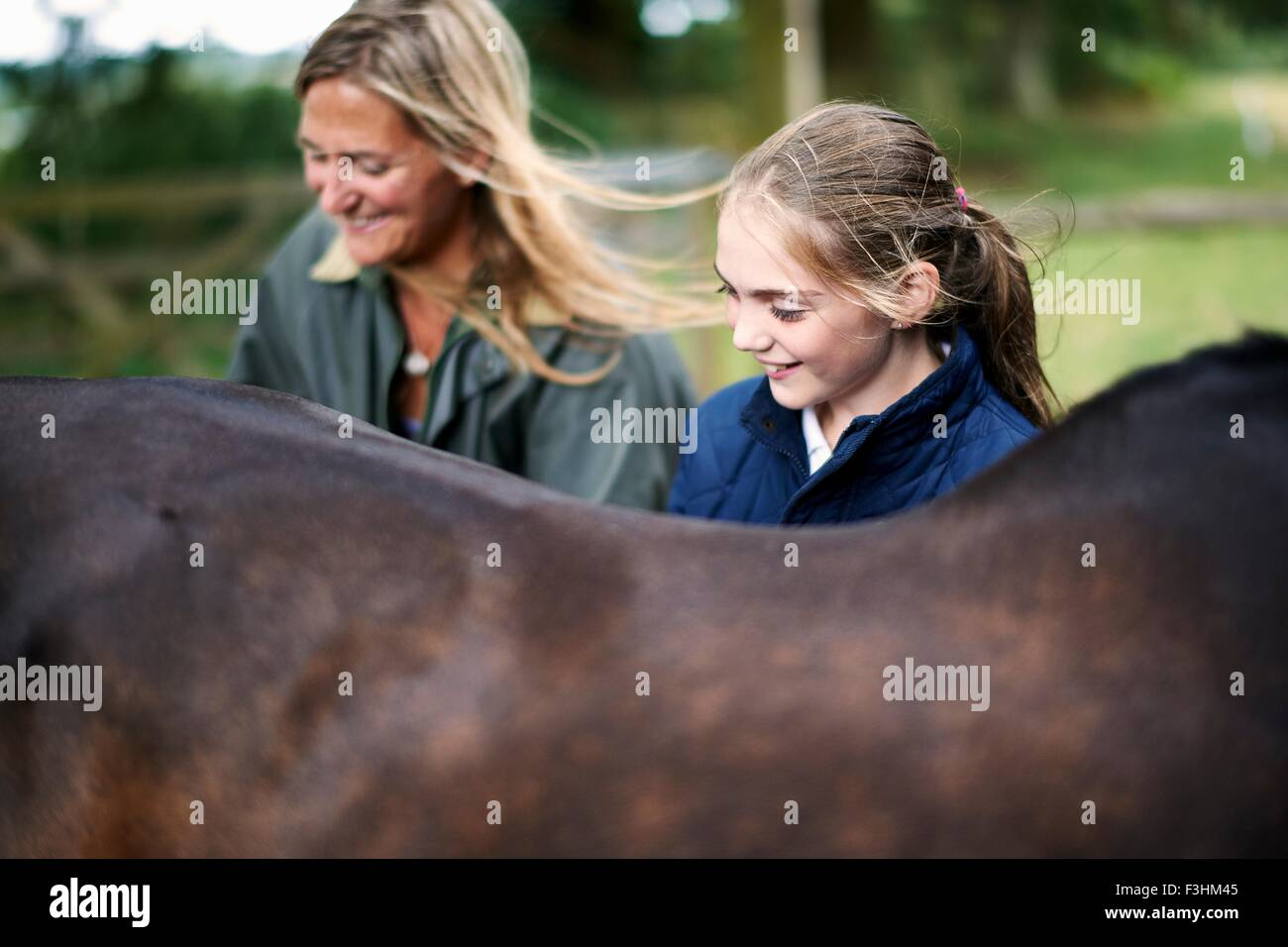 Girl and mother tending horse - Stock Image