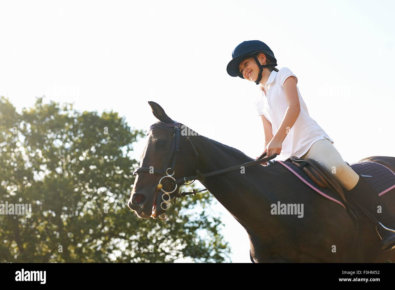 Low angle view of girl riding horse in countryside - Stock Image