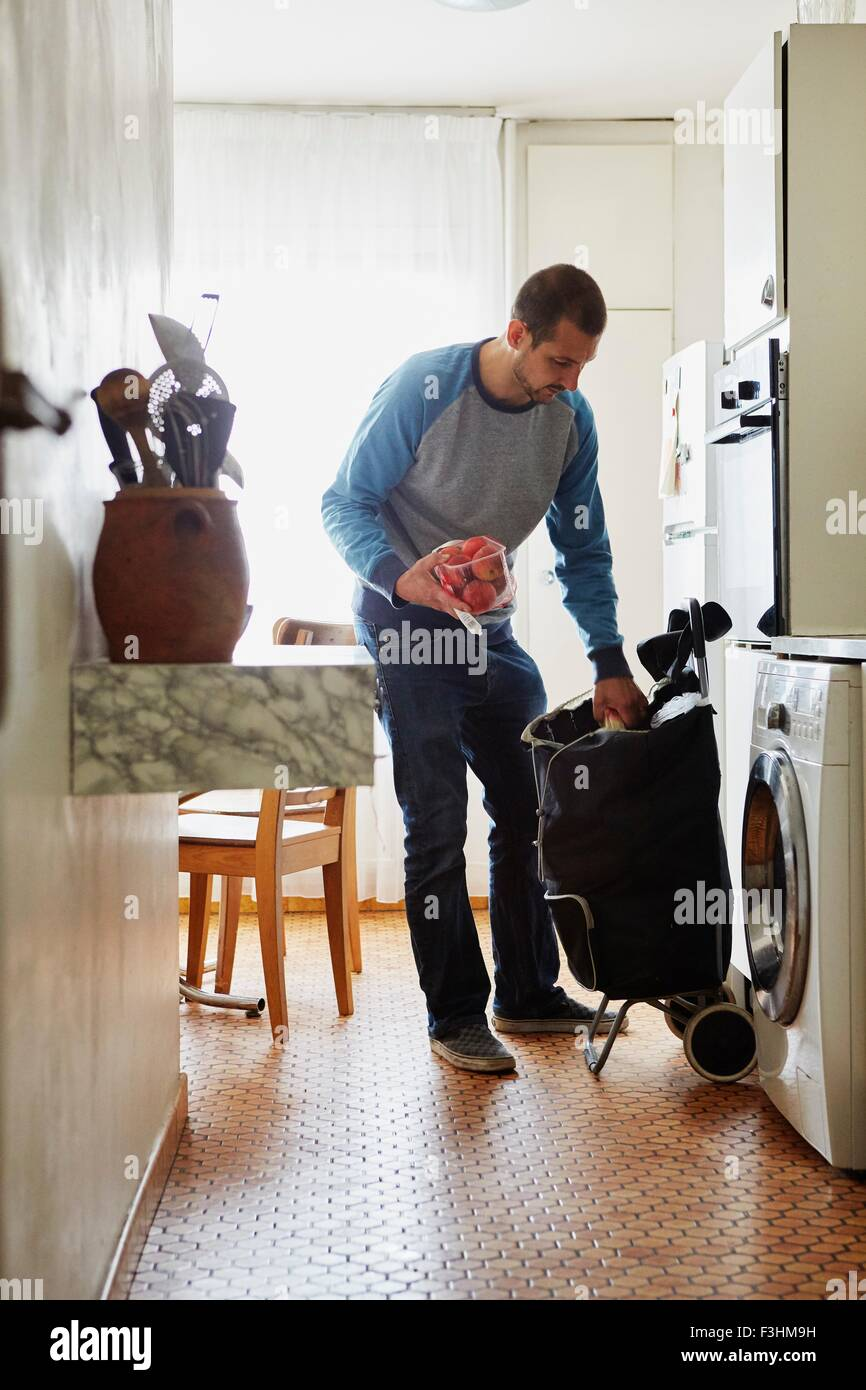 Man unpacking groceries at home - Stock Image