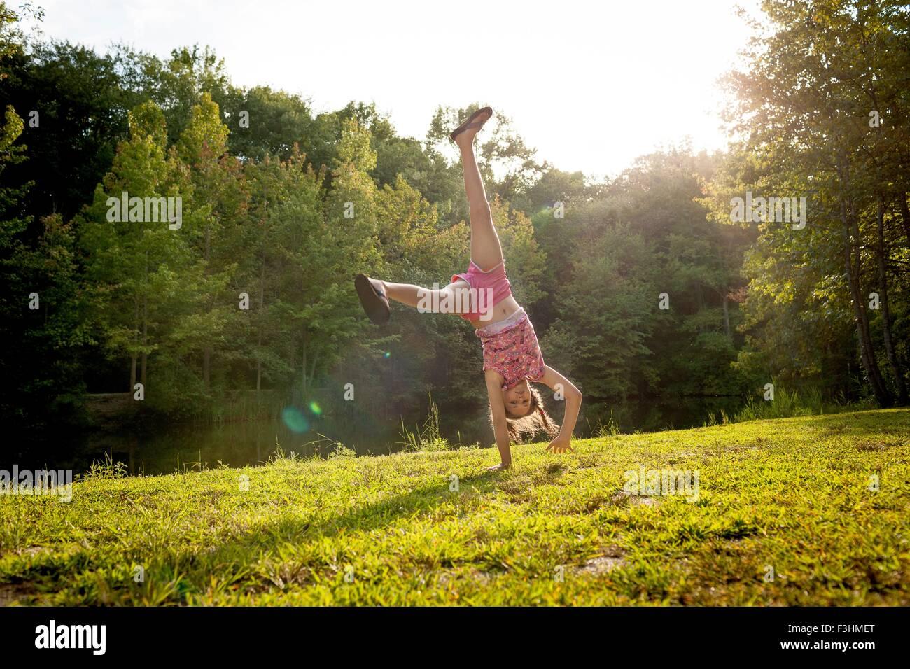 Girl upside down doing cartwheel looking at camera - Stock Image