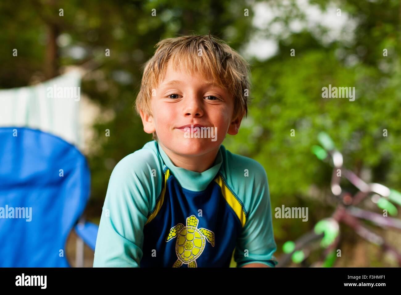 Portrait of boy wearing swimwear looking at camera smiling - Stock Image