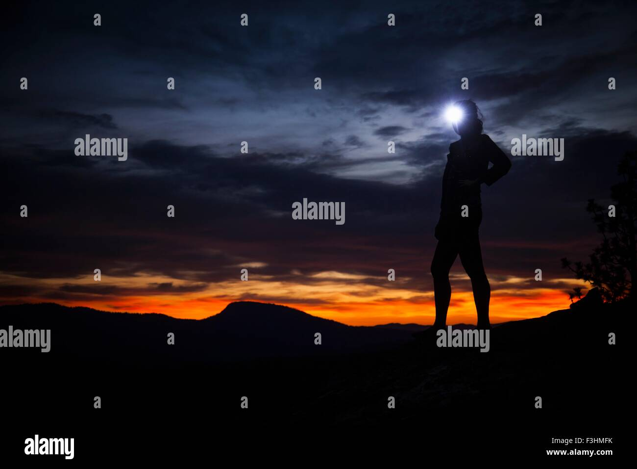 Young woman standing at nights in darkness wearing headlamp - Stock Image