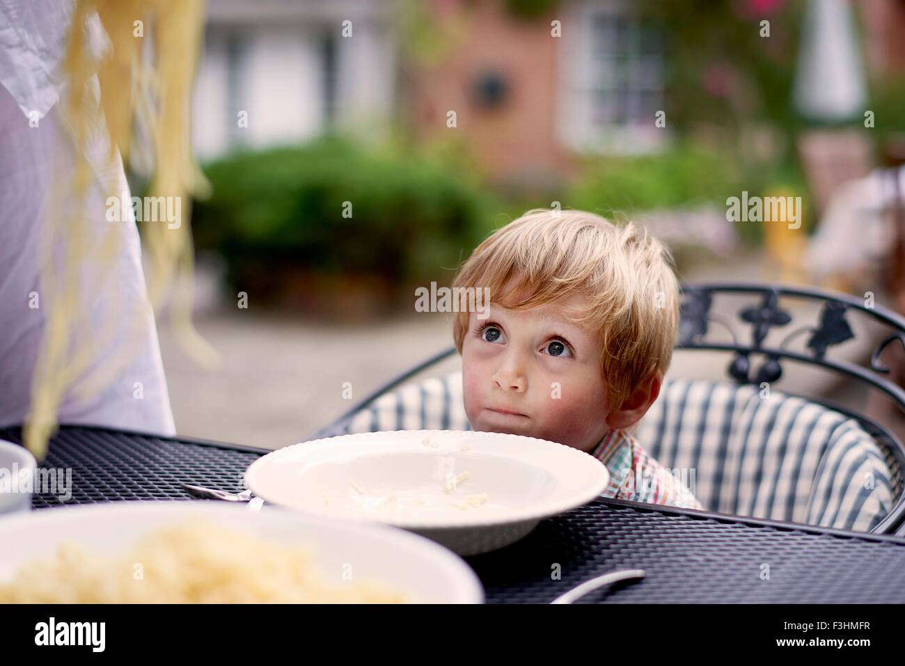 Boy sitting at garden table waiting for spaghetti to be served - Stock Image