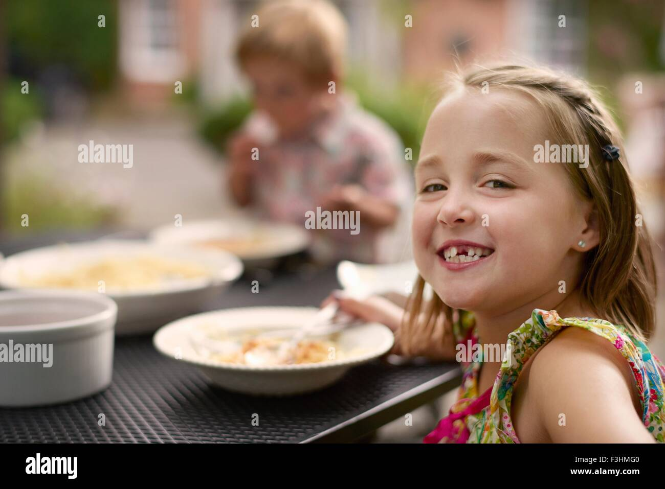 Girl dining at garden table, looking over shoulder smiling at camera - Stock Image