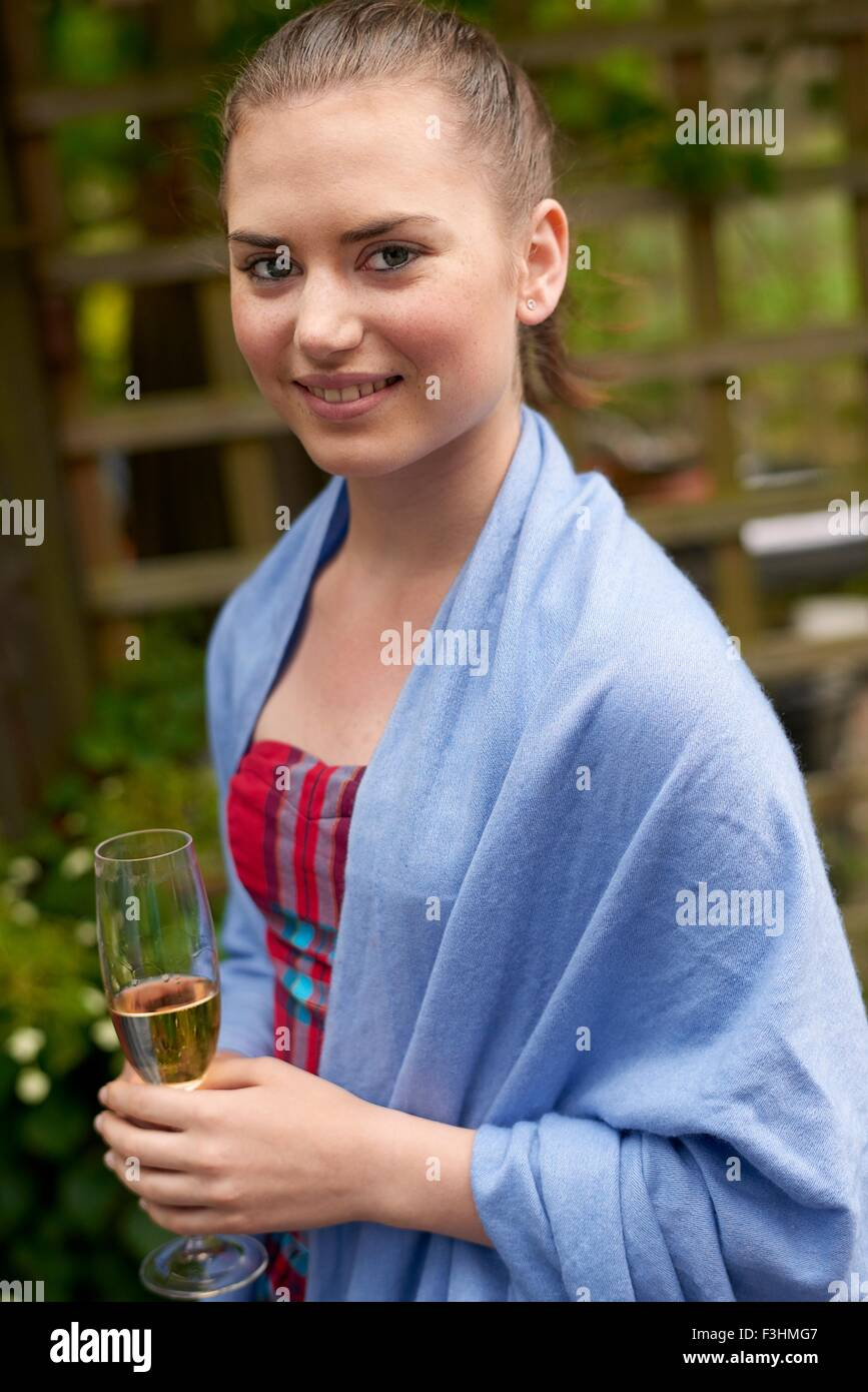 Portrait of teenage girl wearing pashmina, holding champagne flute looking at camera smiling - Stock Image