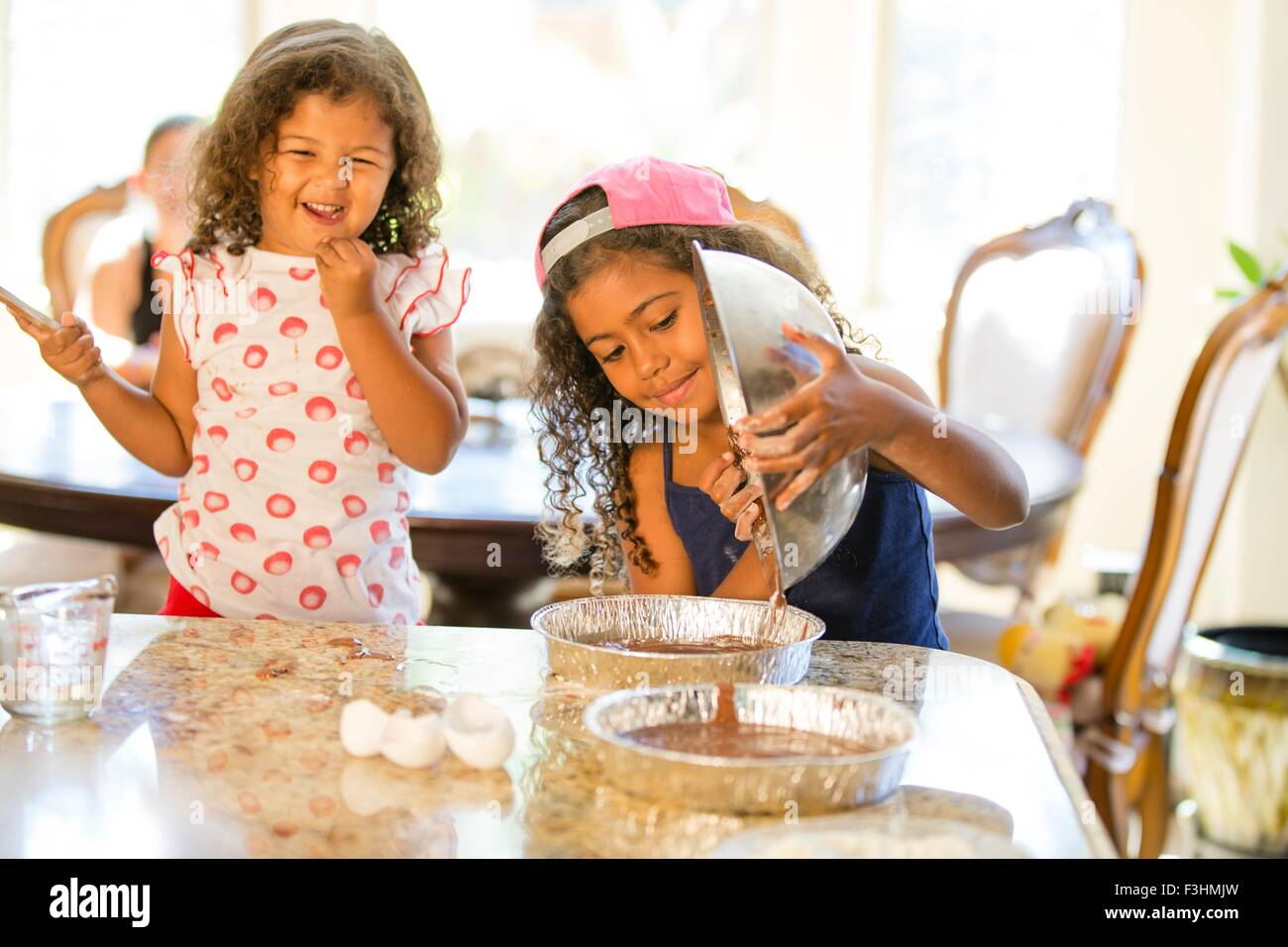 Sisters pouring chocolate cake mix from mixing bowl into cake tins smiling - Stock Image