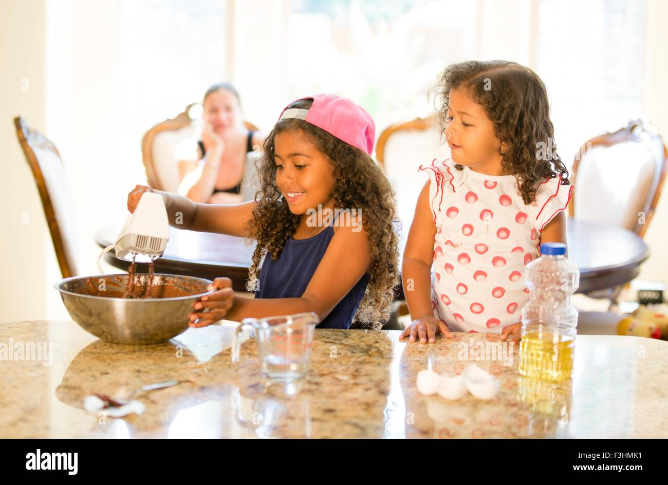 Sisters at kitchen counter whisking choclate cake mix in mixing bowl looking down smiling - Stock Image