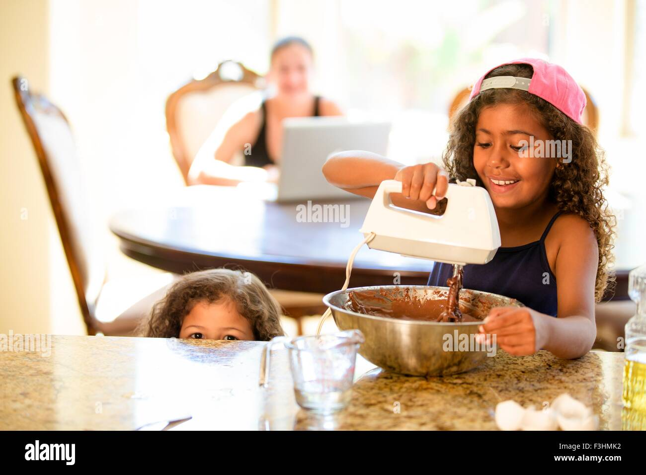 Sisters whisking chocolate cake mix in mixing bowl, smiling - Stock Image