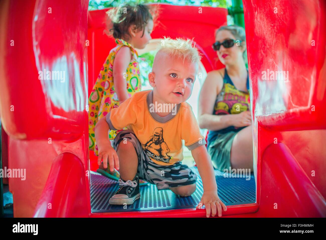 Mother and children playing on red playground slide Stock Photo