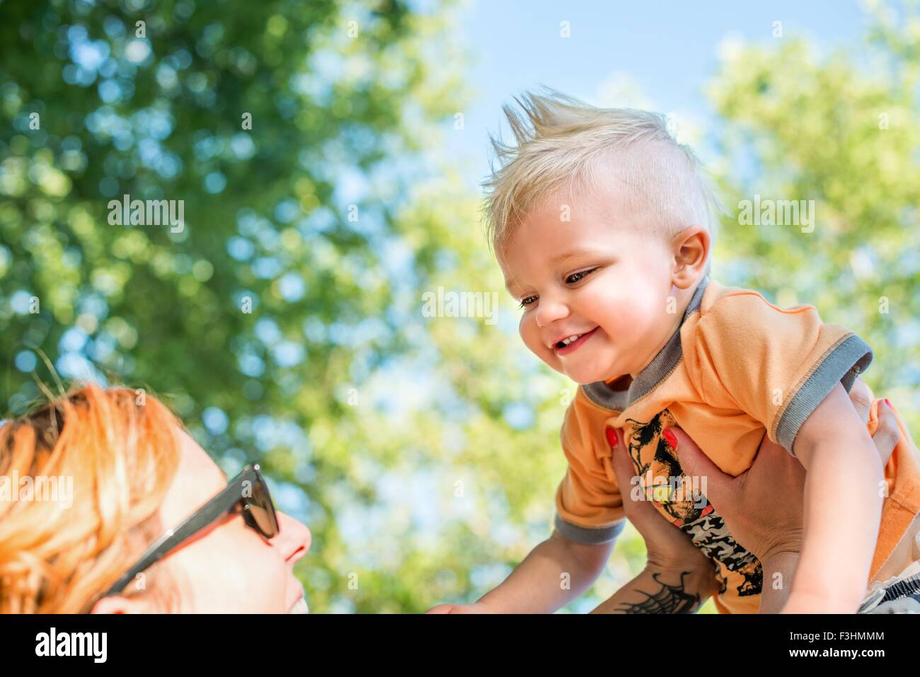 Low angle view of mother holding up smiling baby boy - Stock Image