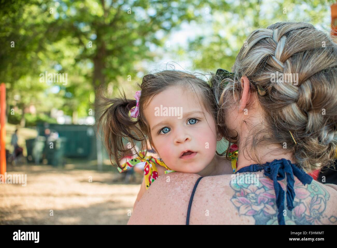 Baby girl looking over mothers shoulder at camera - Stock Image
