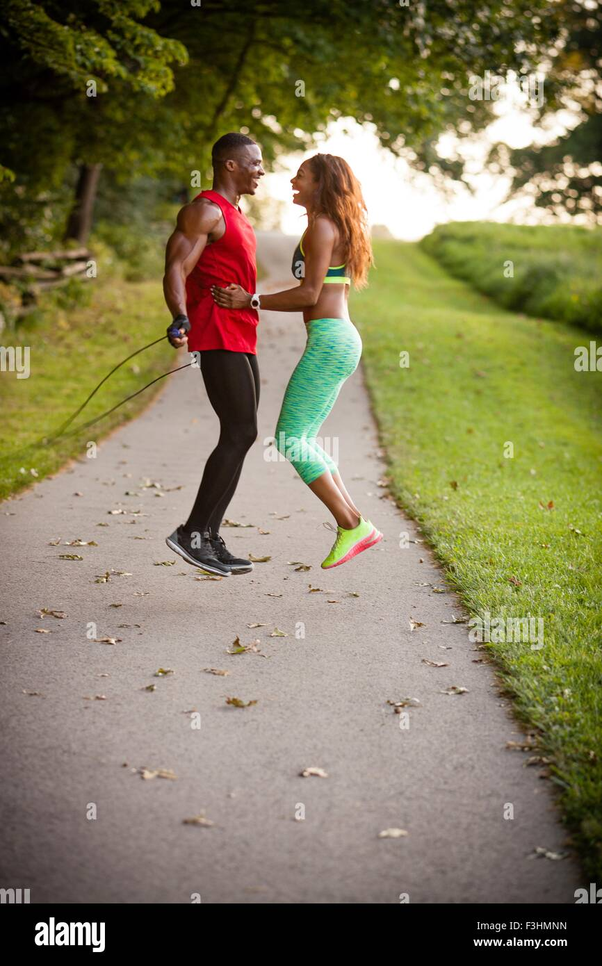 Young couple training on path skipping in unity - Stock Image