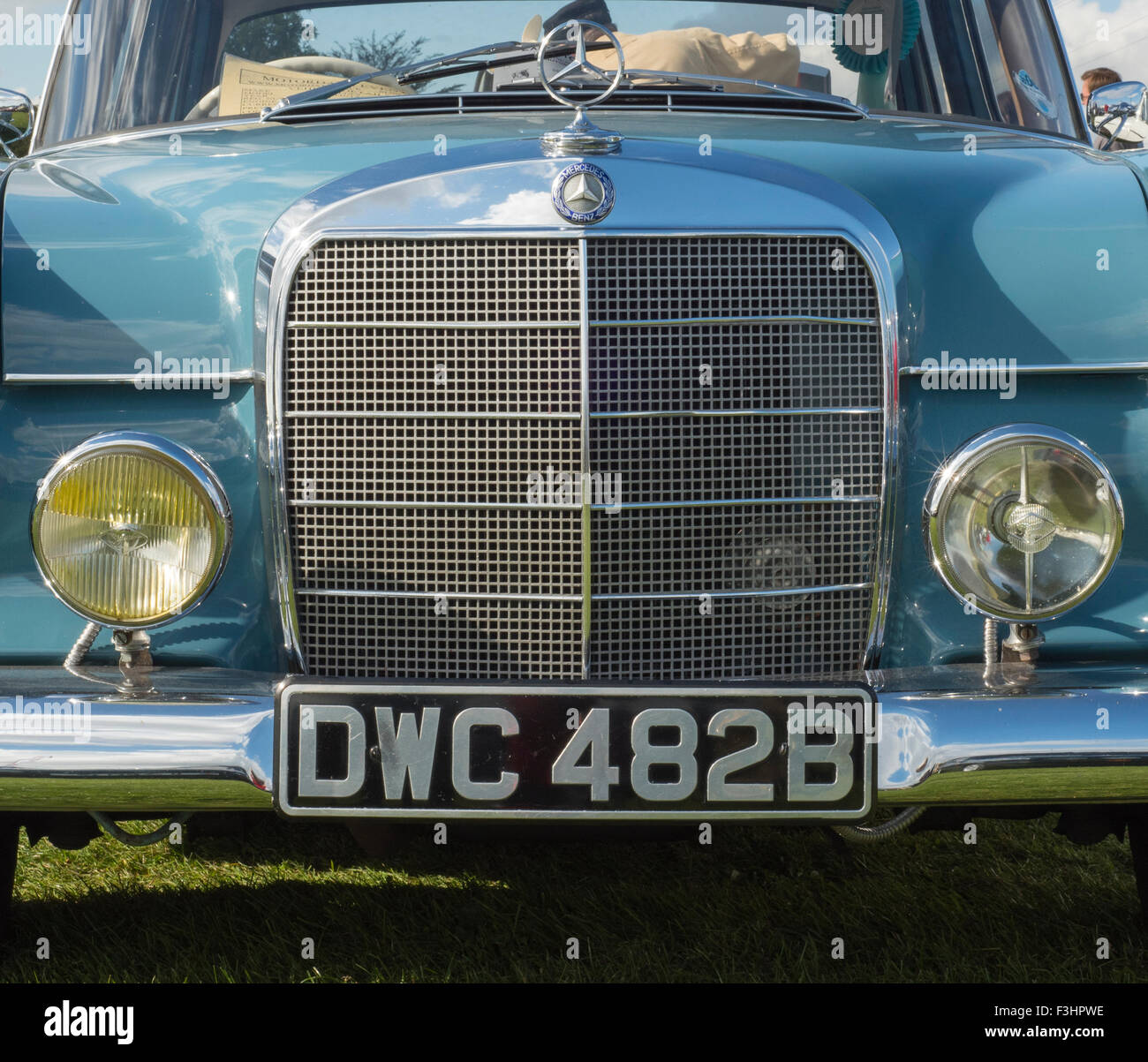 Vintage Blue Mercedes Benz, headlamps, grille, badge, windscreen, windshield, reflection of clouds, shadows, grass, - Stock Image