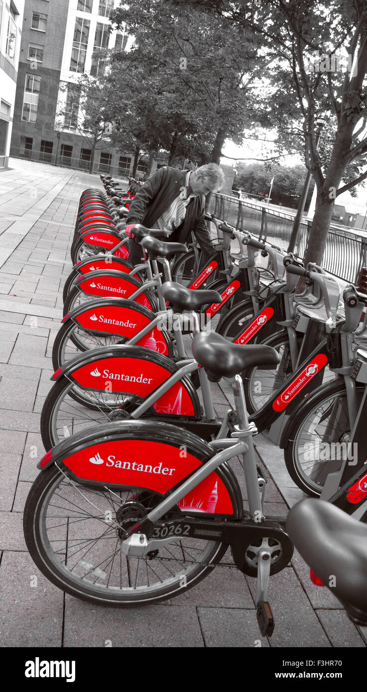TFL London red rental hire bikes in Canary Wharf with new sponsor livery of Santander London UK ( B&W treatment) - Stock Image