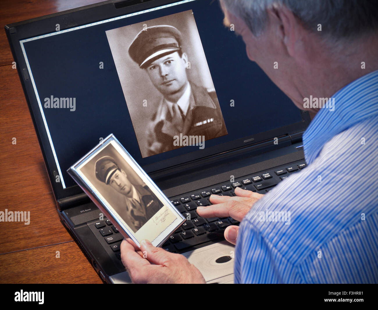 Mature man holding a framed B&W photo with enhanced scanned image of same on computer scree - Stock Image