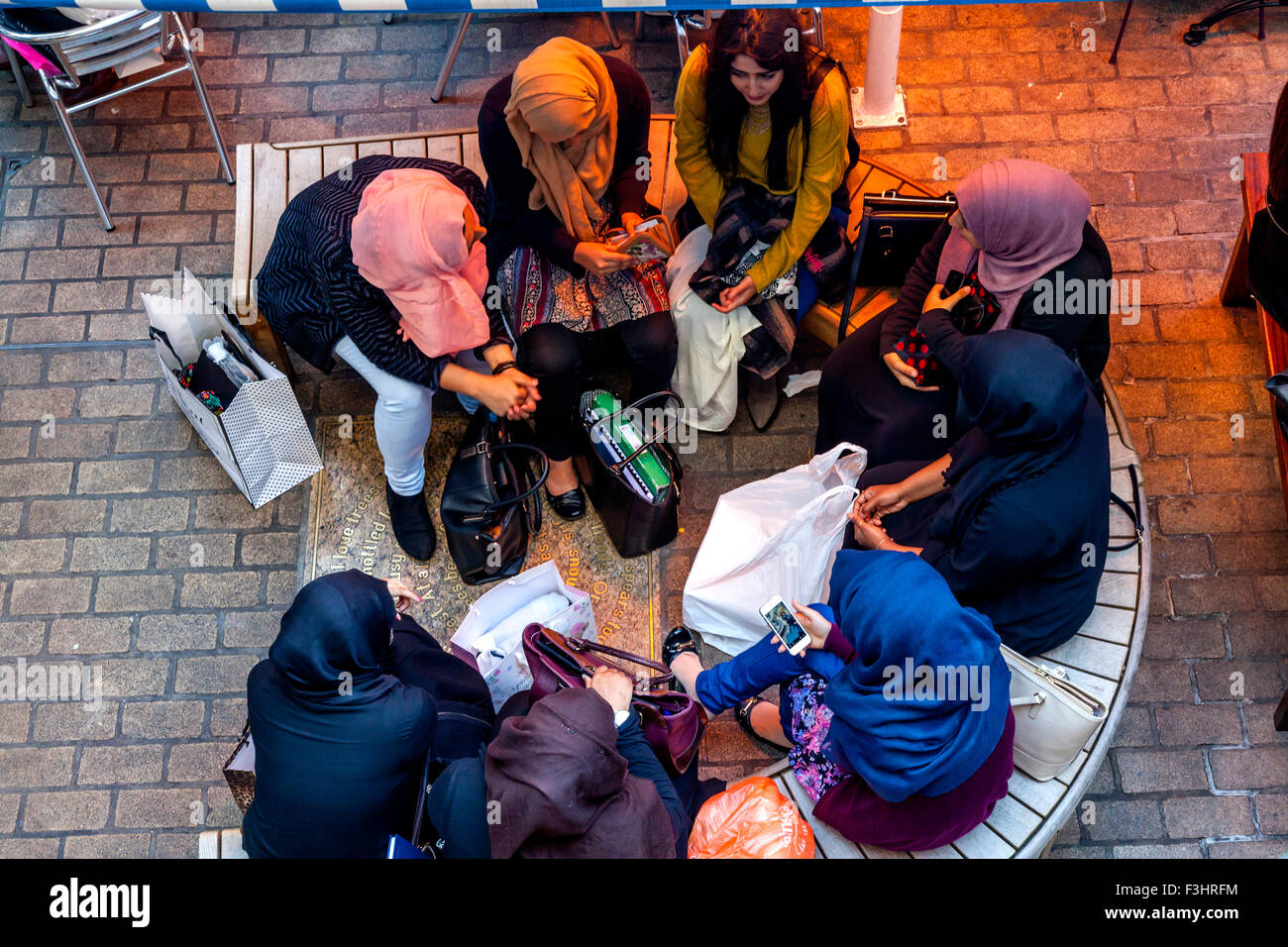 Young Muslim Women Sit Chatting At A Cafe In Carnaby Street, London, UK - Stock Image