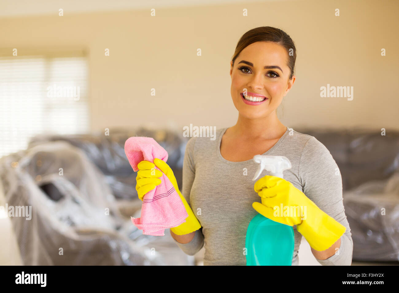 beautiful housewife doing housework in new home - Stock Image