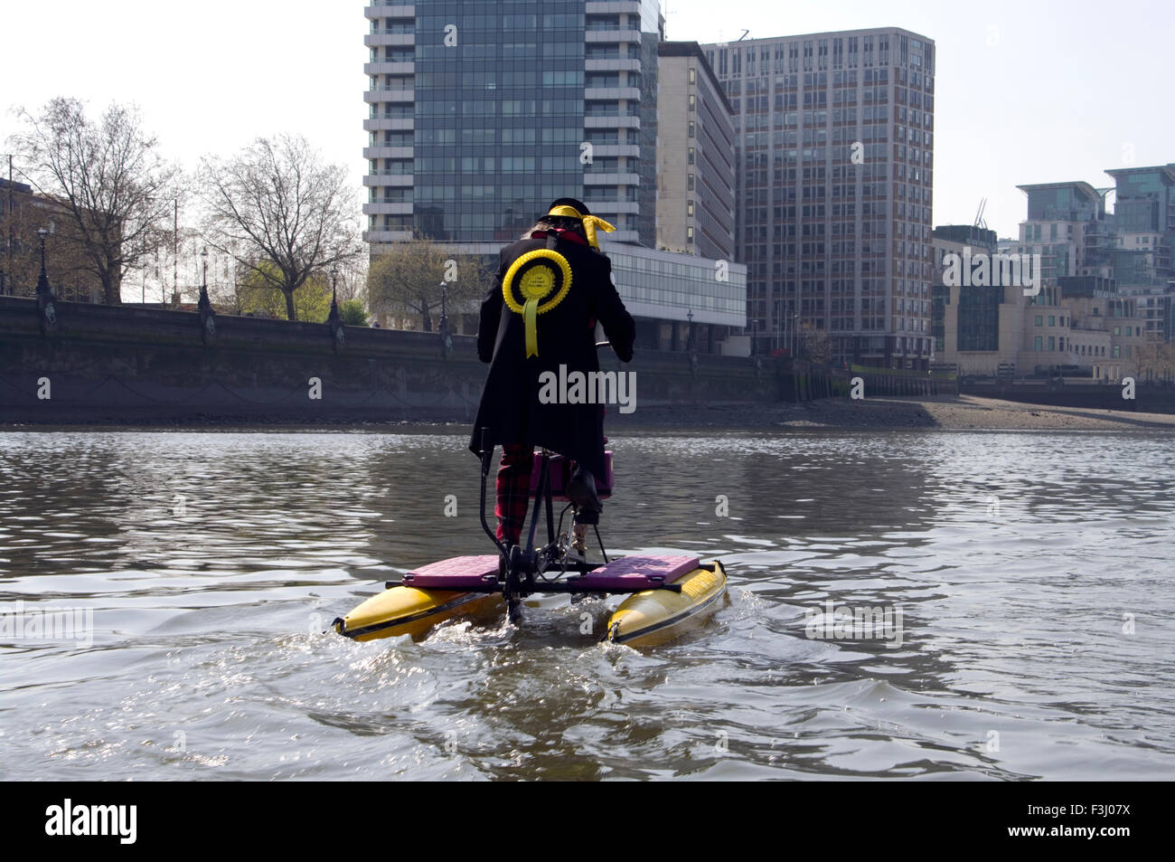 Hackney Monster Raving Loony Party candidate, Nigel Knapp,on floating bicycle on the Thames in front of the House - Stock Image