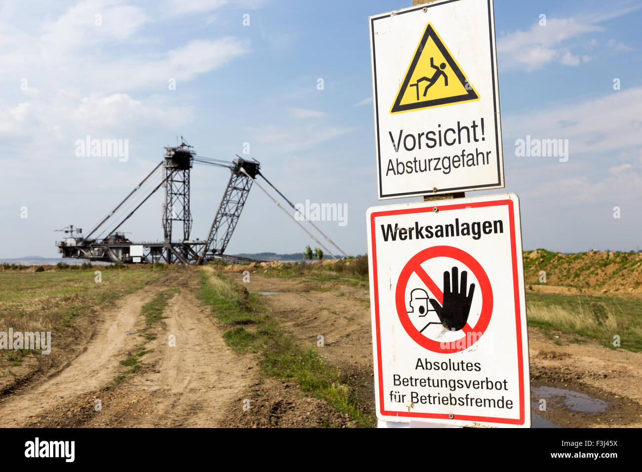 Warning sign near a giant mining excavator at a open pit mine near Cologne. Stock Photo