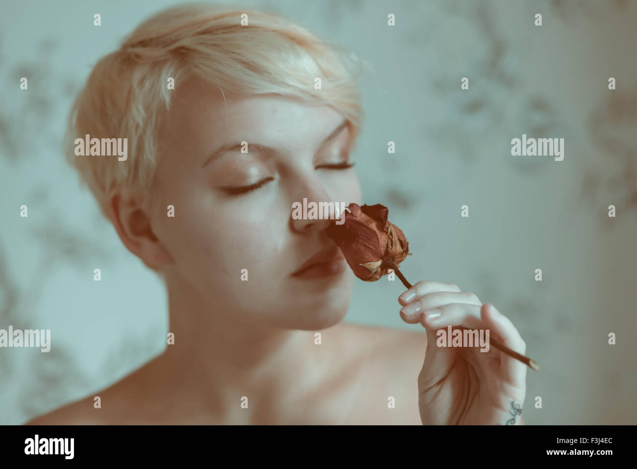 Blond teenage girl holding a dead rose - Stock Image