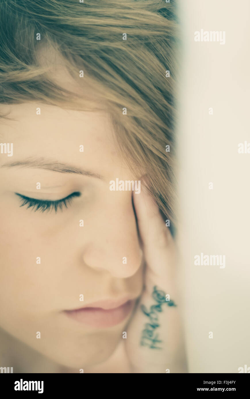 Young teenage girl with her eyes closed upset - Stock Image