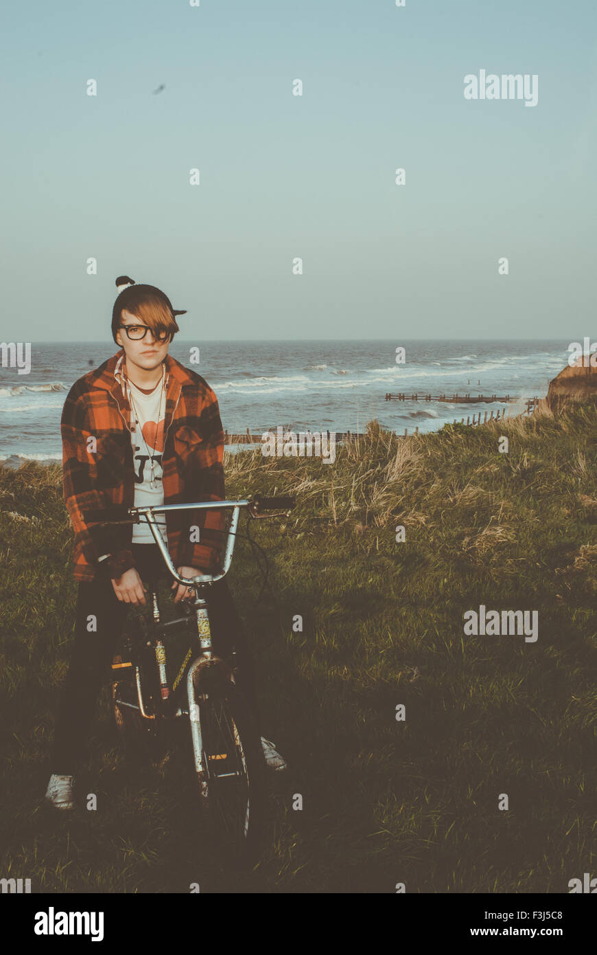 Teenage girl sitting on a bike by the coast - Stock Image
