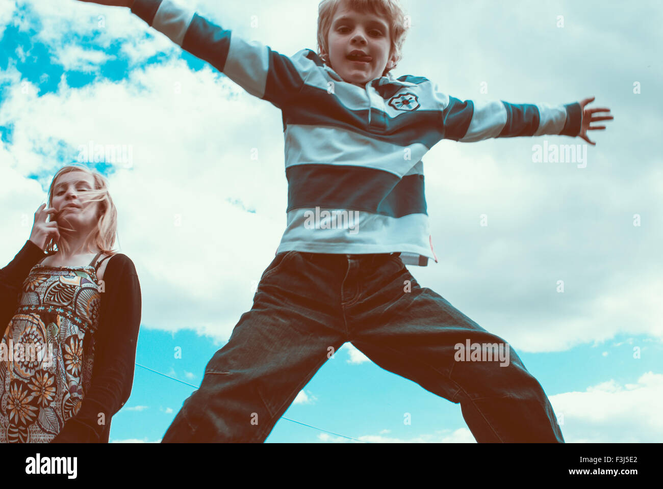 Little kid doing a star jump mid air - Stock Image