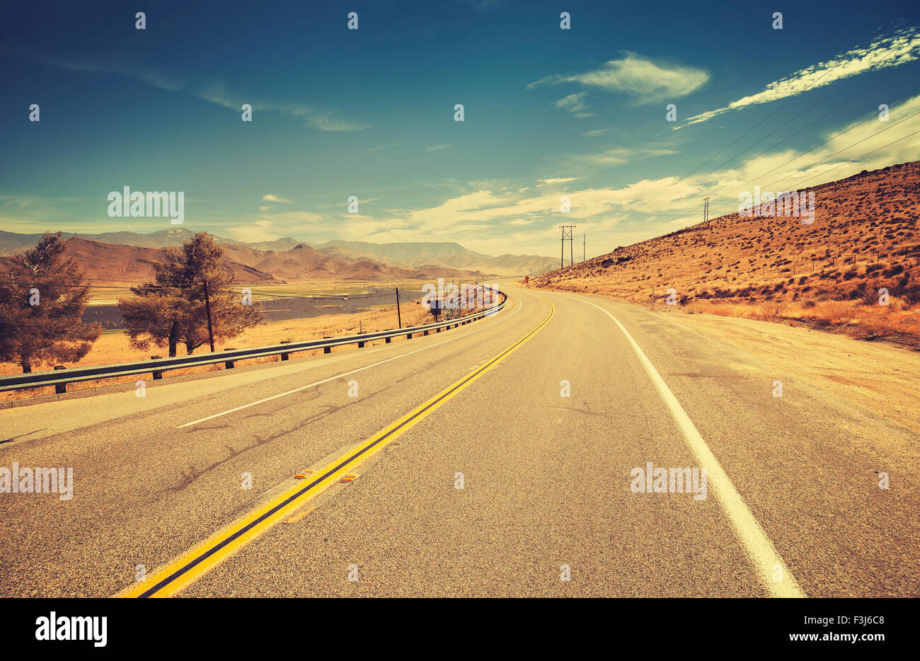 Retro old film style country highway in USA, travel adventure concept. - Stock Image