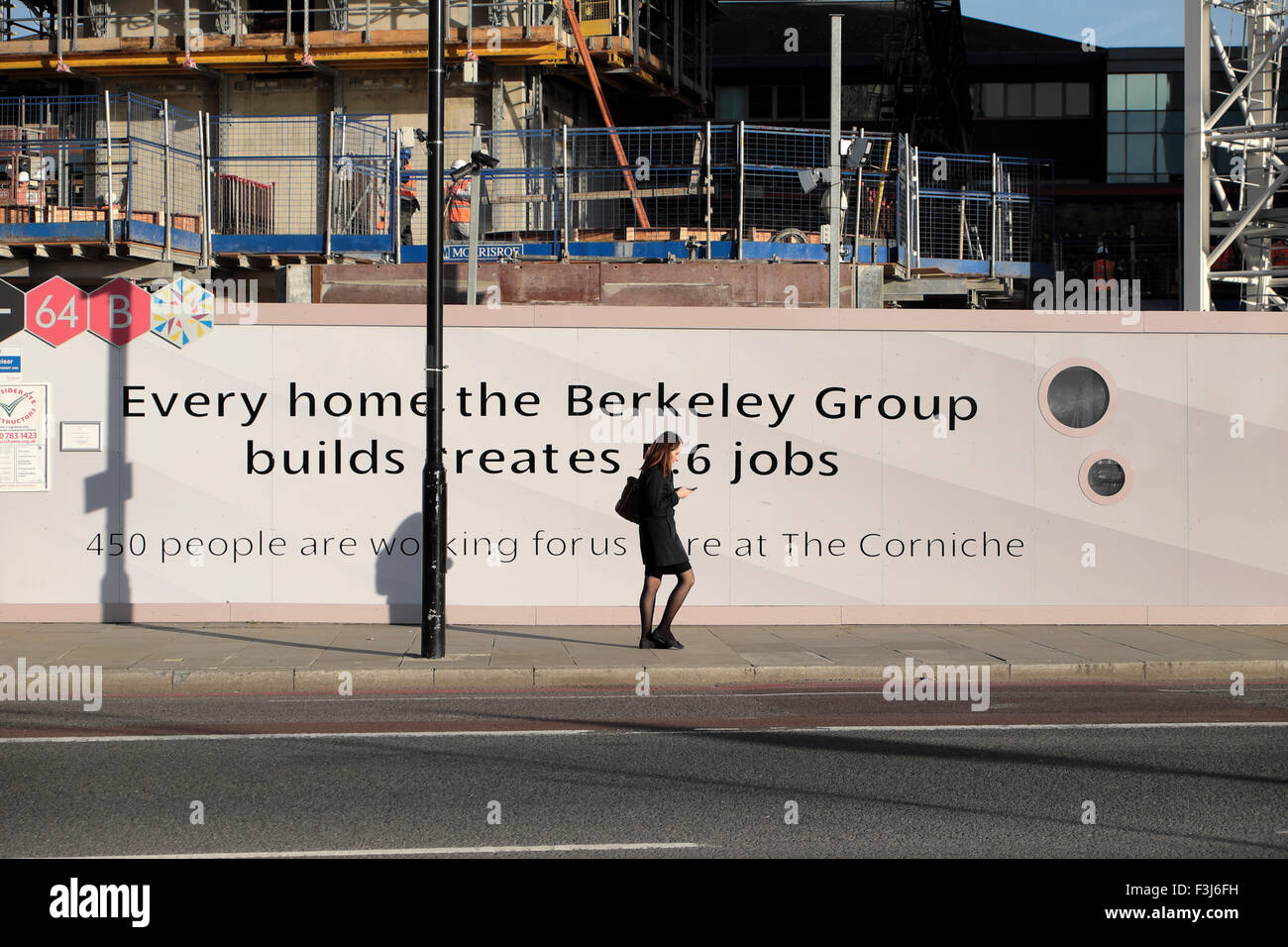 Woman walking past Berkeley Group construction hoarding jobs advert on the Albert Embankment Vauxhall South London - Stock Image