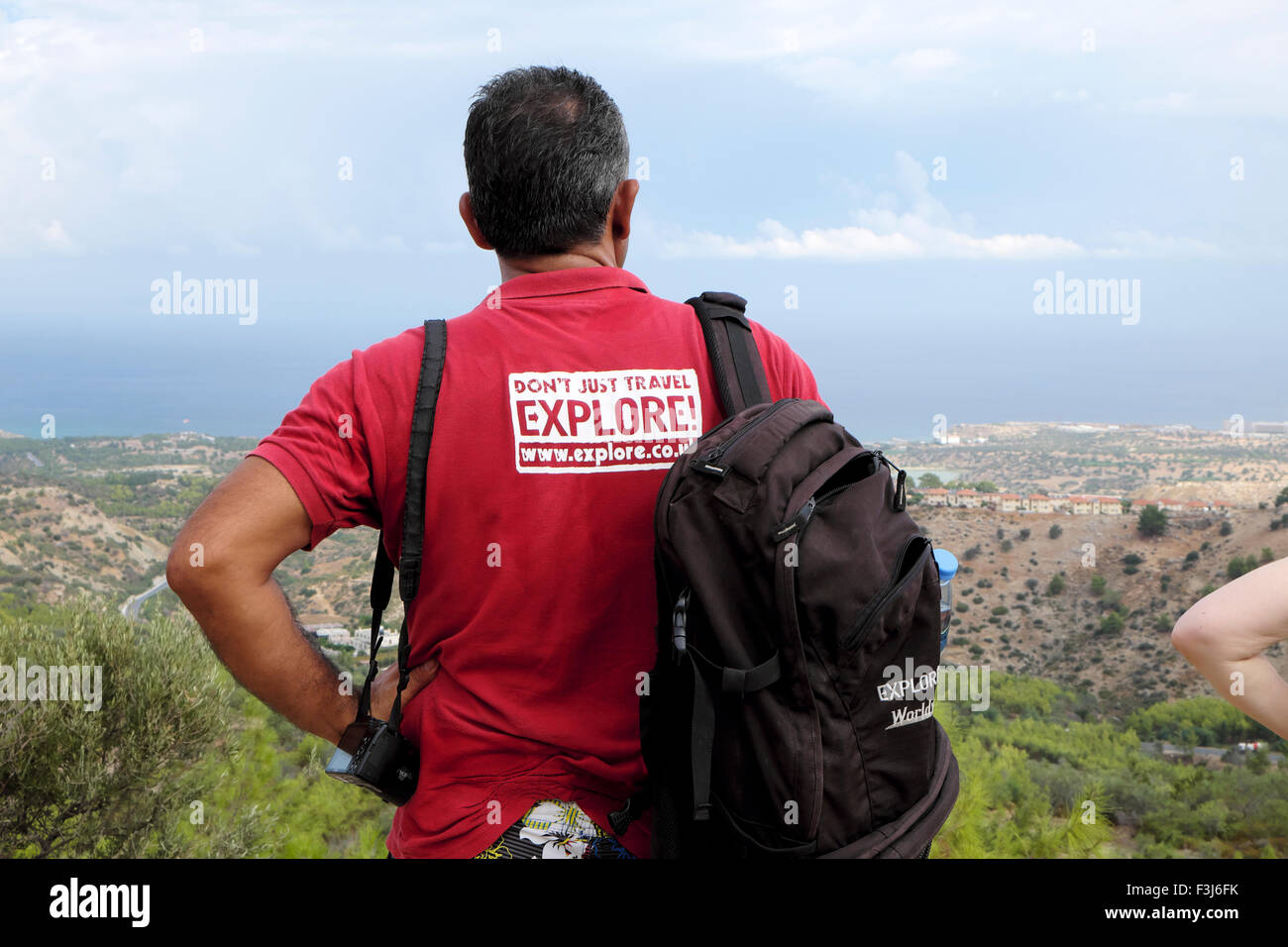 Rear view of an Explore travel guide in red tshirt surveying the landscape in North Cyprus  KATHY DEWITT Stock Photo