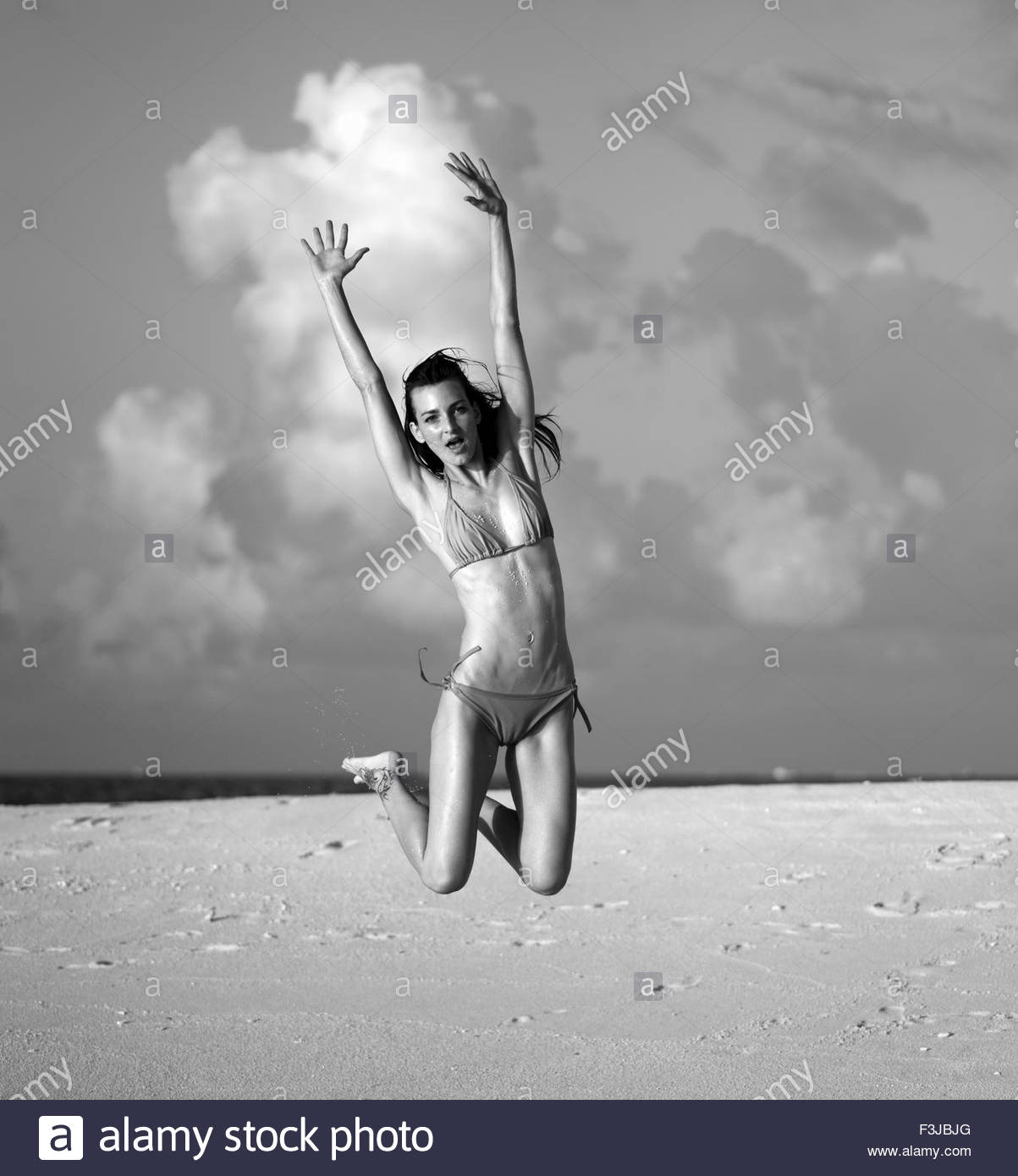 Young Woman Jumping On A Tropical Beach - Stock Image