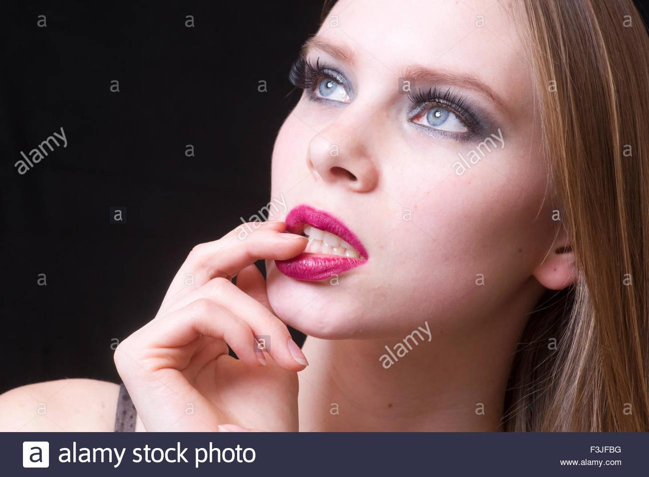 Young Woman's Hand Touching Mouth Studio Shot - Stock Image