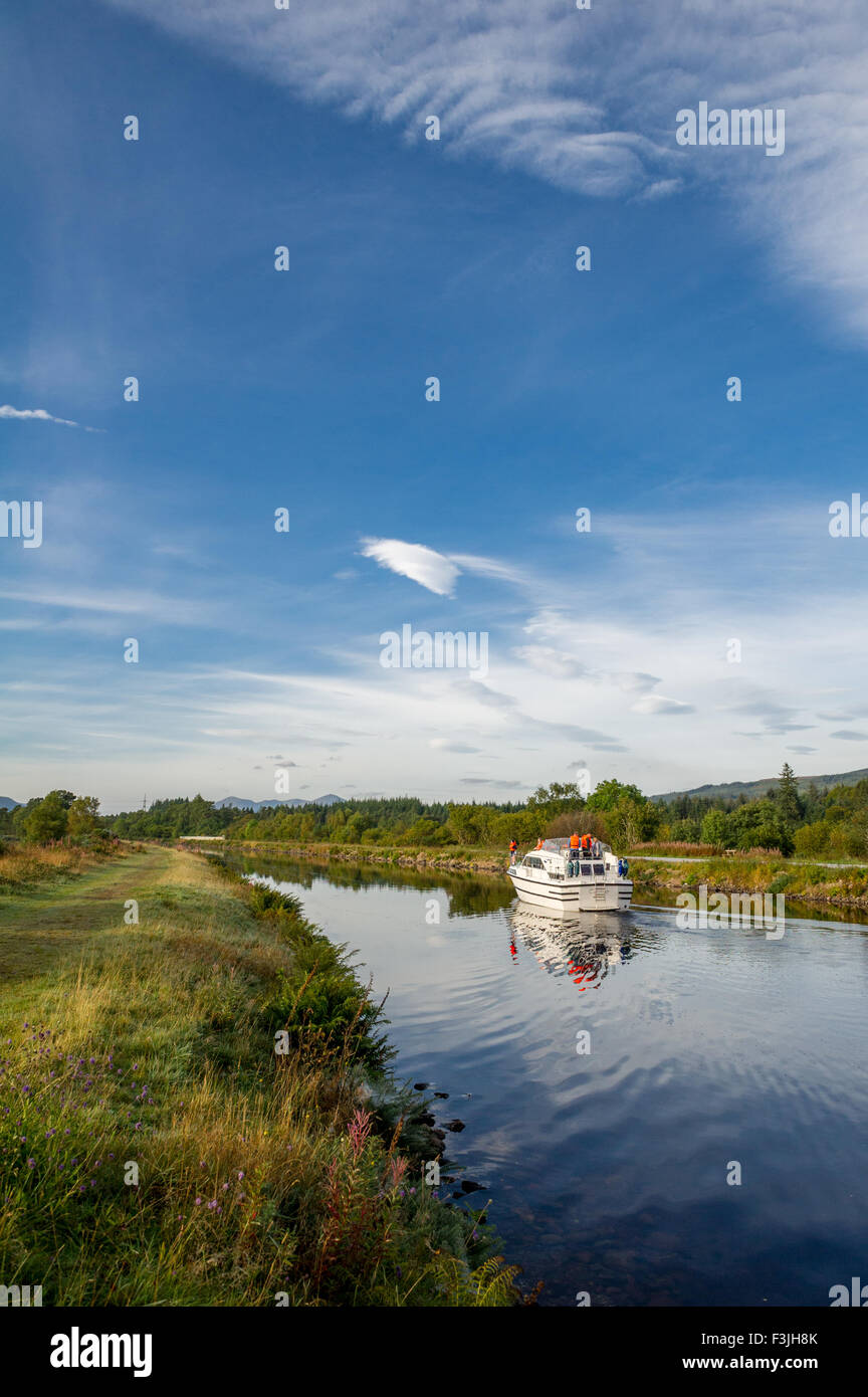 Family on a small motor cruiser cruising along the Caledonian Canal in Scotland. - Stock Image