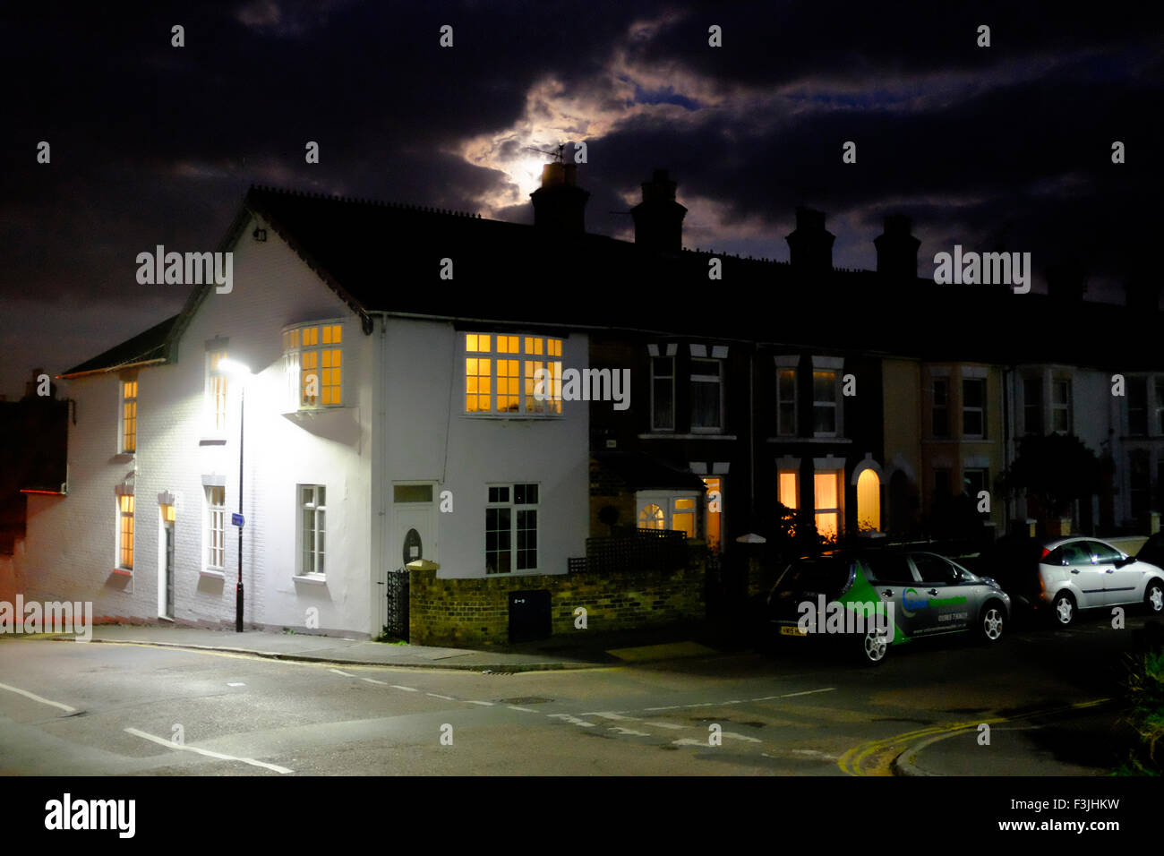 moonrise moon rise night scene houses terrace street lights lighting chimneys windows lit at corner cars parked - Stock Image